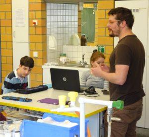 Zu sehen ist ein Chemieraum. Ein Lehrer steht am rechten Bildrand. Er spricht mit mehreren Schülern, die an Tischen sitzen.