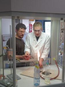 Ein Schüler mit Laborkittel und Schutzbrille und ein Lehrer stehen an einem Abzug. Der Schüler zündet im Abzug die Flamme eines Bunsenbrenners an.