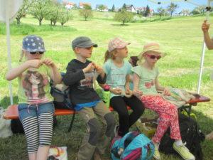 Mehrer Kinder sitzen essend auf einer Bank. Die Bank steht auf einer grünen Wiese.