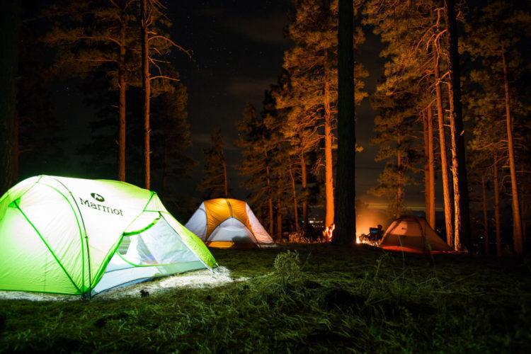 Symbolbild für den Kurs: zwei von innen beleuchtete Zelte im Wald