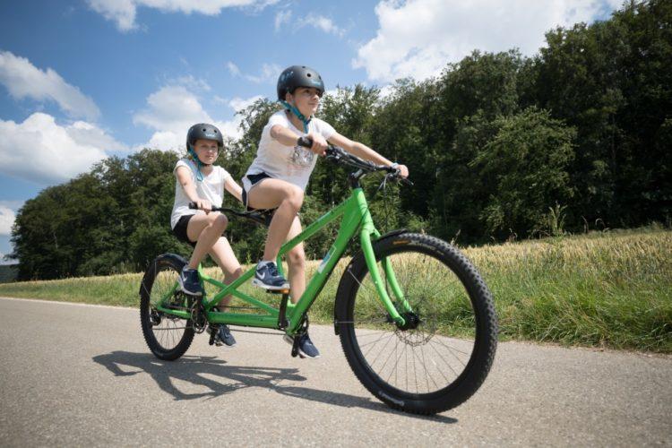 Zwei Kinder fahren auf einem grünen Tandem.