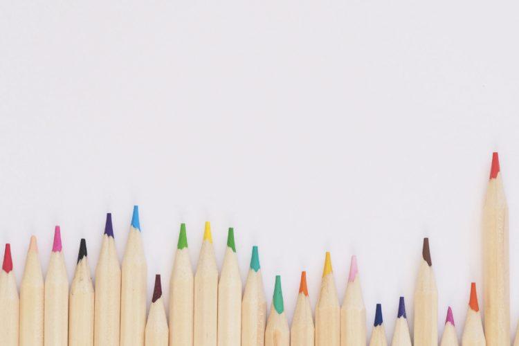 Eine Reihe bunter Holzmalstifte nebeneinander